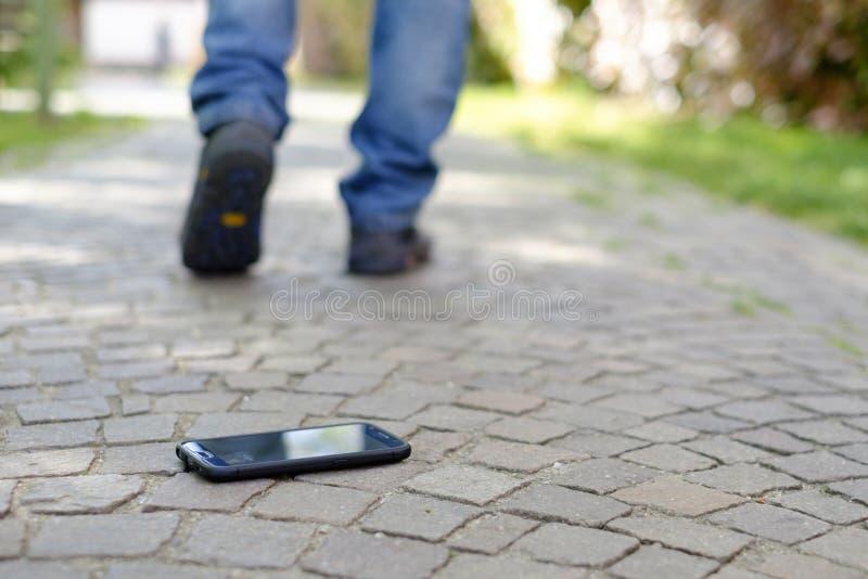 走在丢失的人他的智能手机以后 库存照片