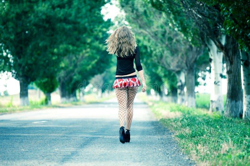 走在乡下公路的美丽的妇女 免版税库存照片