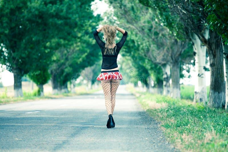 走在乡下公路的美丽的妇女 图库摄影