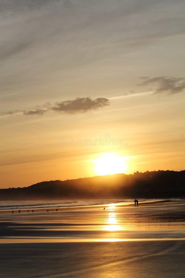 走在五颜六色的日出夏天天空的沙滩的人剪影与反射 图库摄影