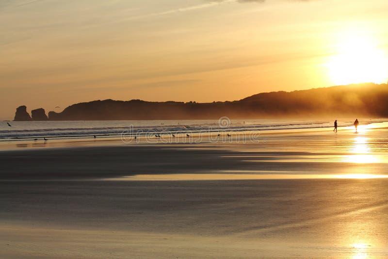 走在五颜六色的日出夏天天空的沙滩的人美妙的剪影与反射 图库摄影