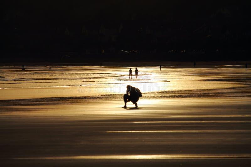 走在五颜六色的日出夏天天空的沙滩的人美妙的剪影与反射 免版税库存照片