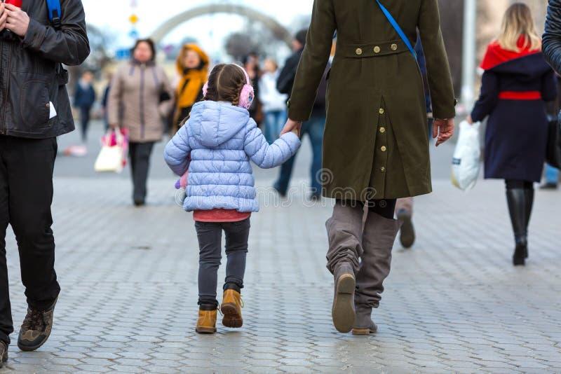 走在人群中的城市街道上的母亲和女儿 免版税库存照片