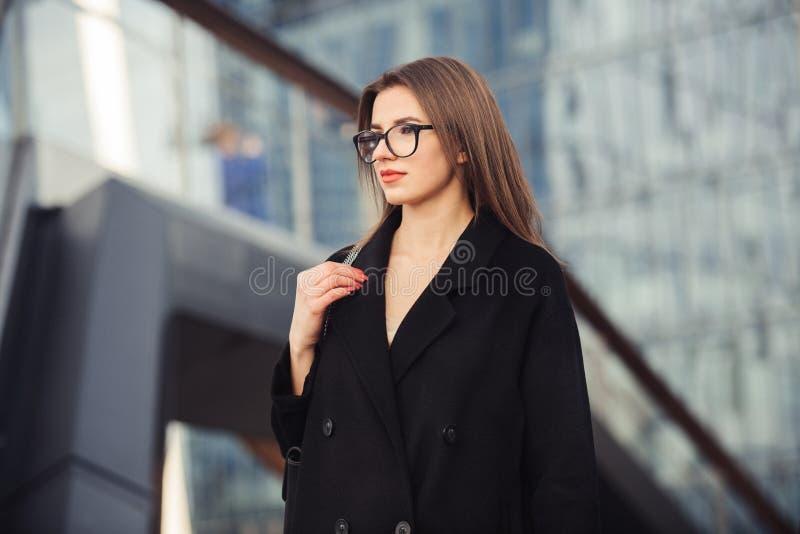 走在从办公室佩带的镜片的城市街道上的美丽的女商人 免版税库存照片