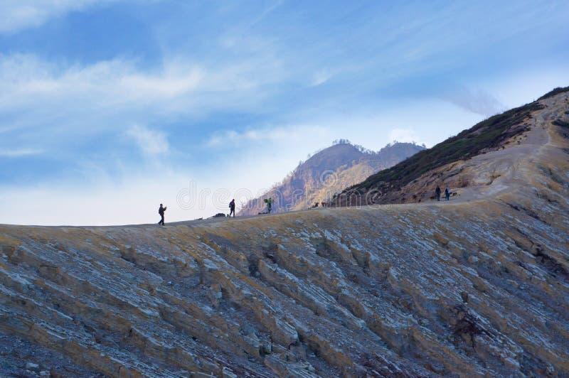 走在伊真火山火山的游人和矿工 免版税库存照片