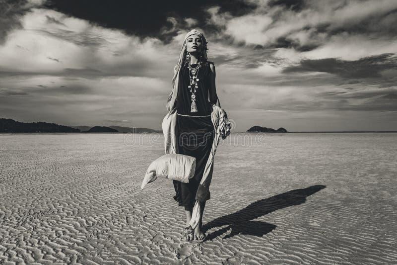 走在低潮的美丽的年轻时髦的妇女在日落 Bl 免版税库存照片