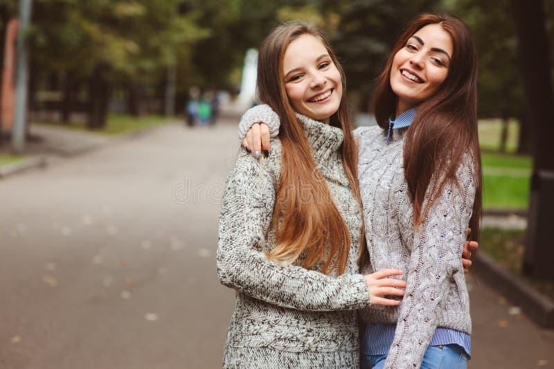 走在偶然时尚成套装备的城市街道上的两个年轻愉快的女朋友 库存照片