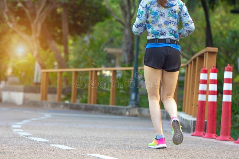 走在公园室外,运动员女性赛跑者赛跑,亚洲运动员跑步和锻炼的年轻健身妇女在早晨 体育, 免版税库存图片