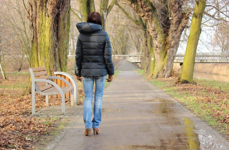 走在公园的孤独的妇女在冷的雨天 库存照片