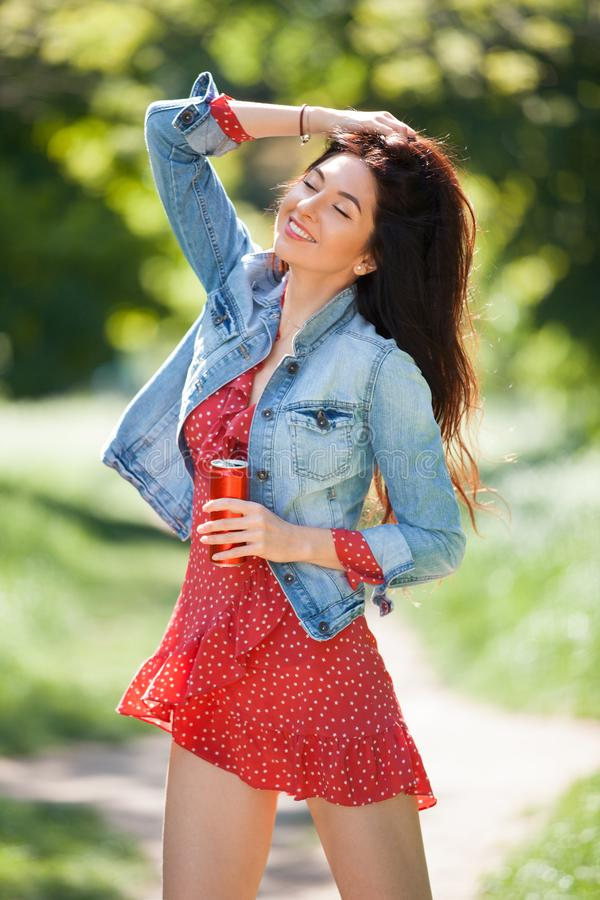 走在公园的年轻女人 秀丽自然场面有五颜六色的背景 有瓶的时尚妇女饮料放松在夏天 免版税图库摄影