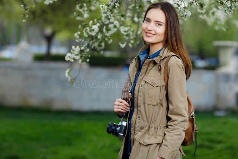 走在公园的年轻美丽的妇女 有葡萄酒照相机的旅客 免版税库存照片