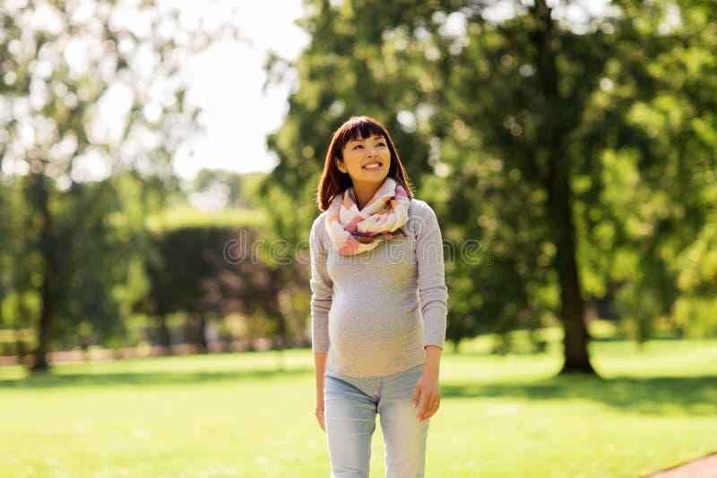 走在公园的愉快的怀孕的亚裔妇女 库存图片