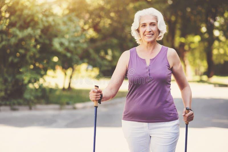 走在公园的愉快的年迈的妇女 免版税库存图片