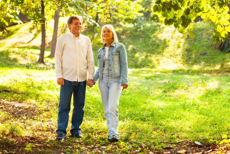 走在公园的成熟夫妇 免版税库存图片