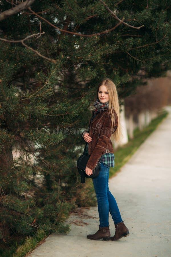 走在公园的白肤金发的女孩 摆在摄影师 图库摄影