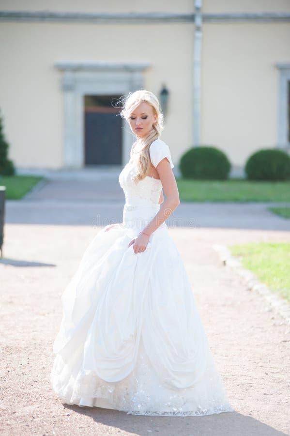 走在公园的美丽的新娘在城堡附近 库存照片