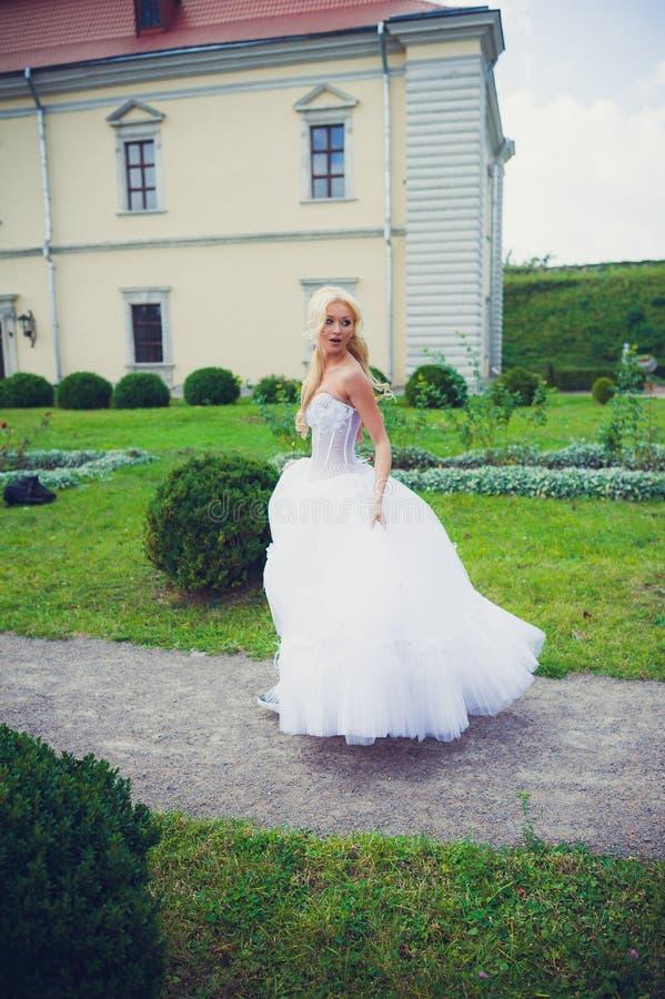 走在公园的美丽的新娘在城堡附近 免版税图库摄影