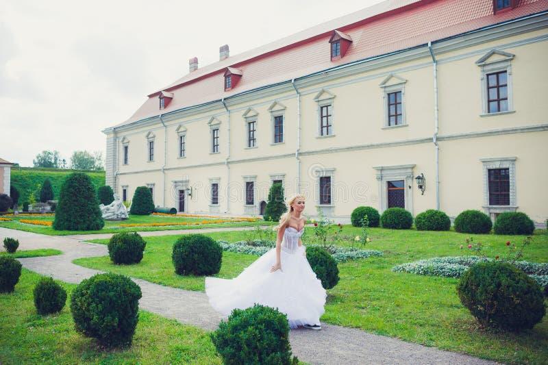 走在公园的美丽的新娘在城堡附近 免版税库存图片