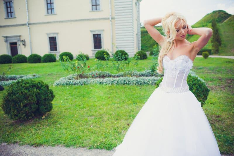 走在公园的美丽的新娘在城堡附近 免版税库存照片