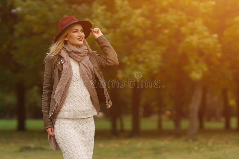 走在公园的美丽的白肤金发的女孩 免版税库存照片