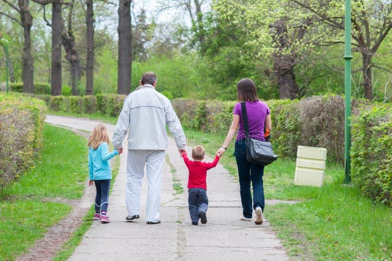 走在公园的年轻家庭在美好的春日 库存图片
