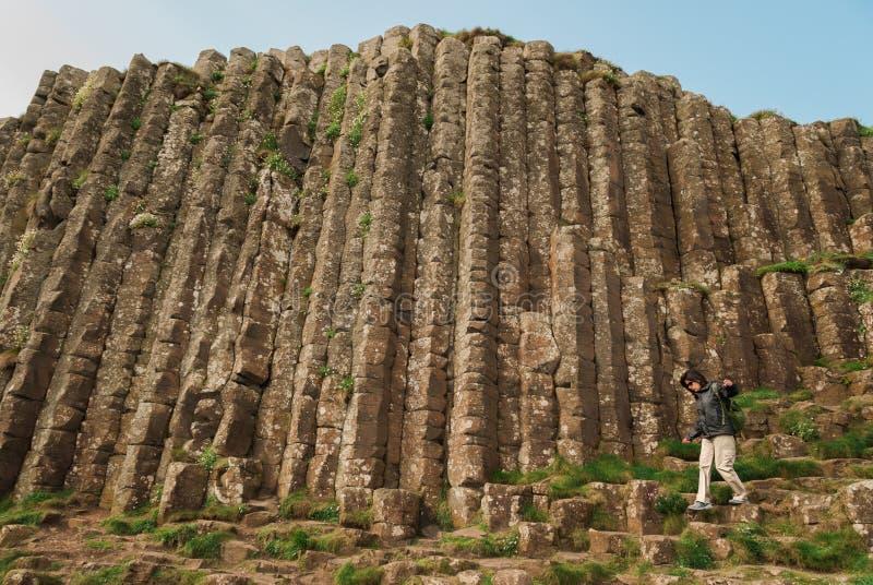 走在六角石头中的妇女在巨型` s堤道 免版税库存图片