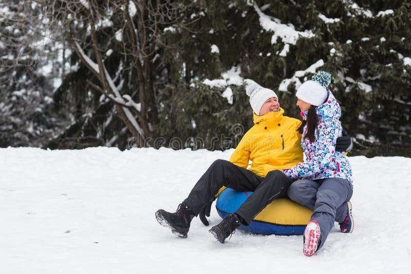 走在冬天公园的年轻愉快的夫妇 免版税库存照片