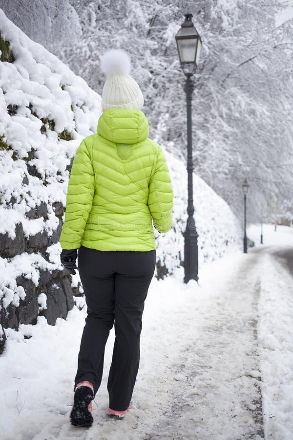 走在冬天城市公园的妇女 免版税库存图片