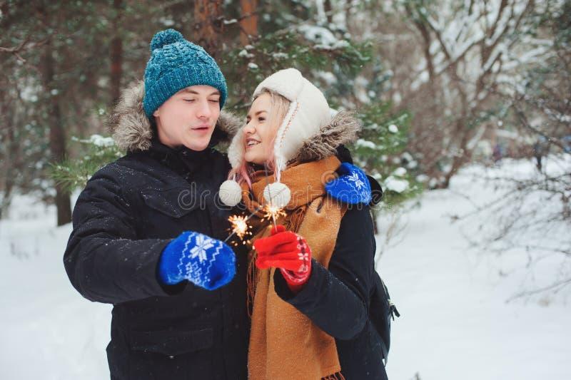 走在冬天多雪的森林里的愉快的年轻夫妇 免版税库存图片
