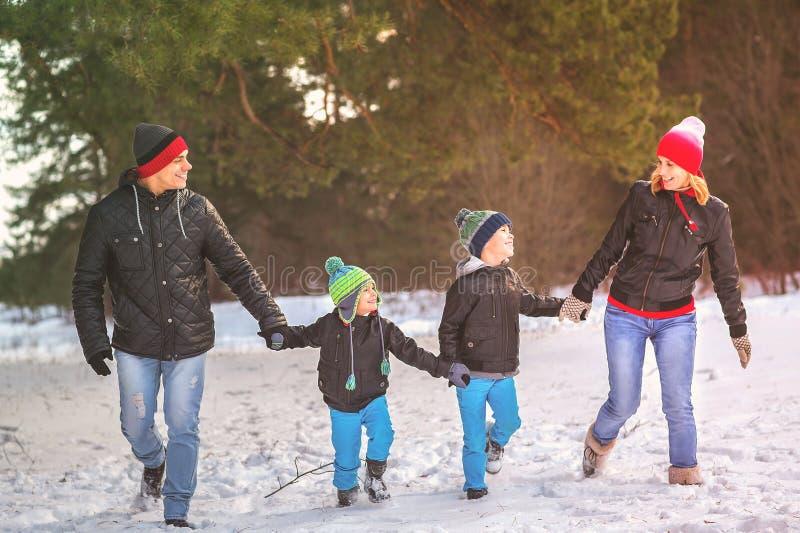 走在冬天森林里的幸福家庭画象 免版税库存照片