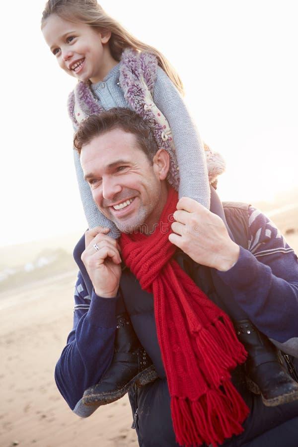 走在冬天海滩的父亲和女儿 免版税图库摄影