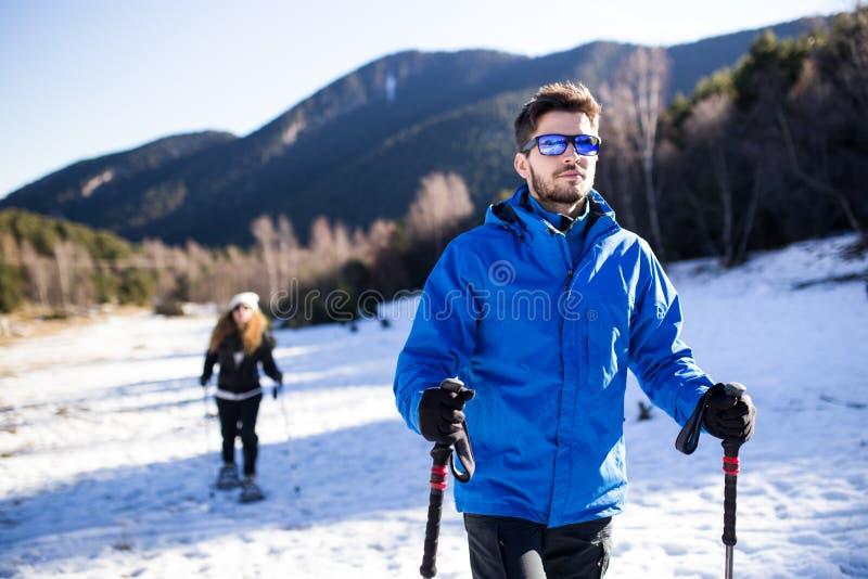 走在冬天背景的雪靴的年轻夫妇 免版税库存图片