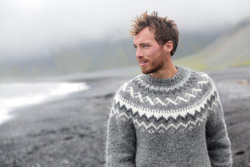 走在冰岛黑沙子海滩的英俊的人 免版税库存图片