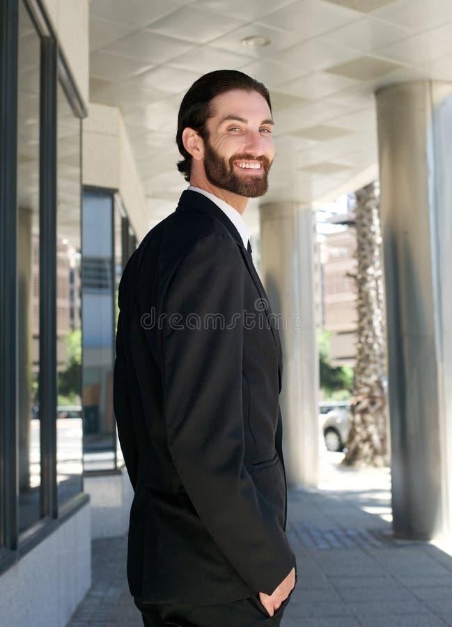 走在办公楼之外的城市的愉快的商人 免版税库存图片