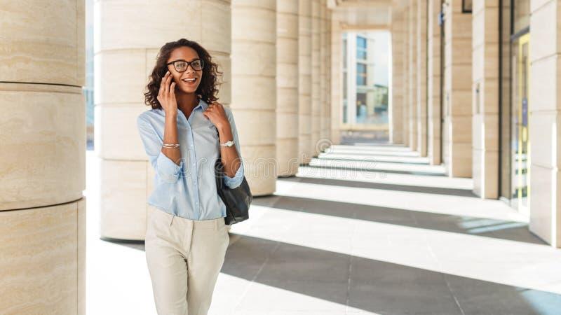 走在办公楼之外的微笑的女实业家 免版税库存照片