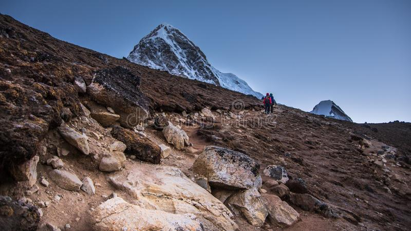 走在卡拉Patthar上面的风景观点的道路和两个登山人  库存图片