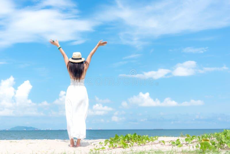 走在含沙海洋海滩的微笑的妇女佩带的时尚白色礼服夏天,美好的蓝天背景 愉快的妇女enj 免版税库存图片