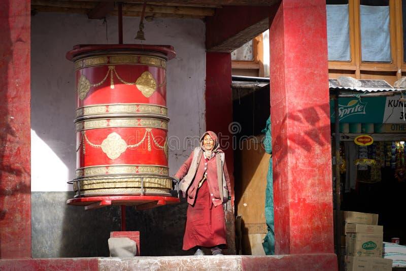 走在圆的佛教鼓附近的老妇人 免版税库存照片