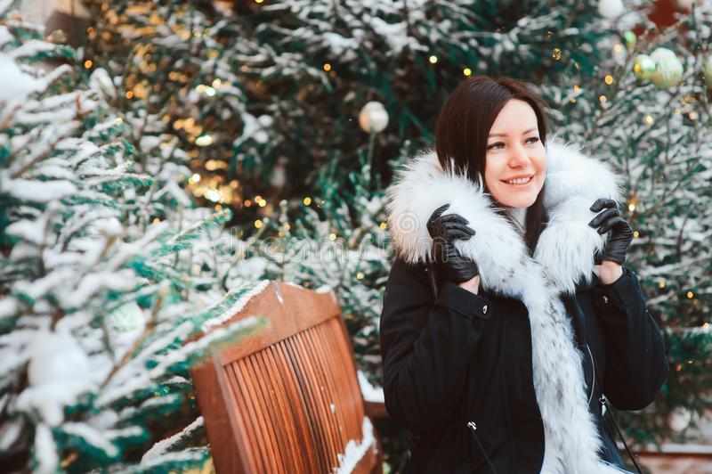 走在圣诞节城市街道的愉快的少妇冬天画象,装饰用诗歌选、玩具和树,佩带的时尚c 库存图片