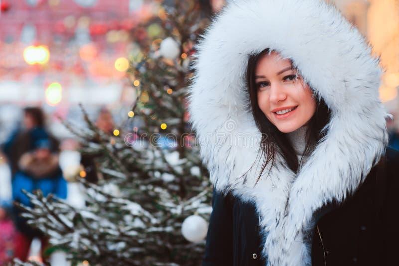 走在圣诞节城市街道的愉快的少妇冬天画象,装饰用诗歌选、玩具和树 免版税图库摄影