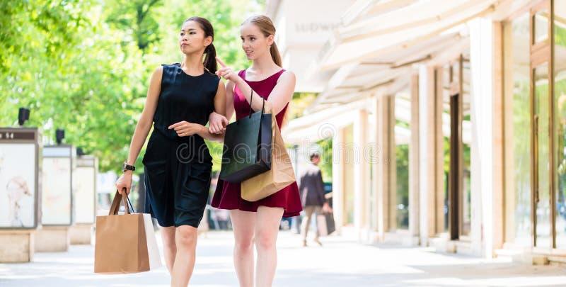 走在城市的两个时兴的少妇在购物期间 免版税库存照片