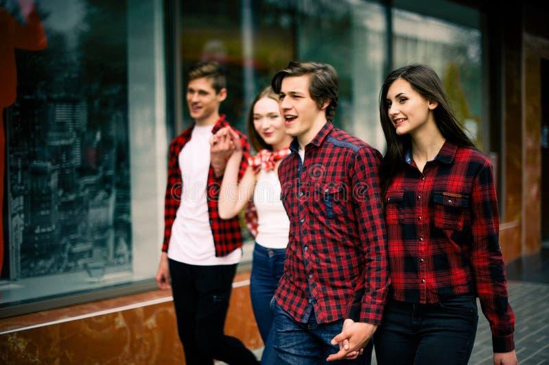走在城市的四个愉快的时髦少年朋友,谈和微笑 生活方式、友谊和都市生活concep 免版税库存图片