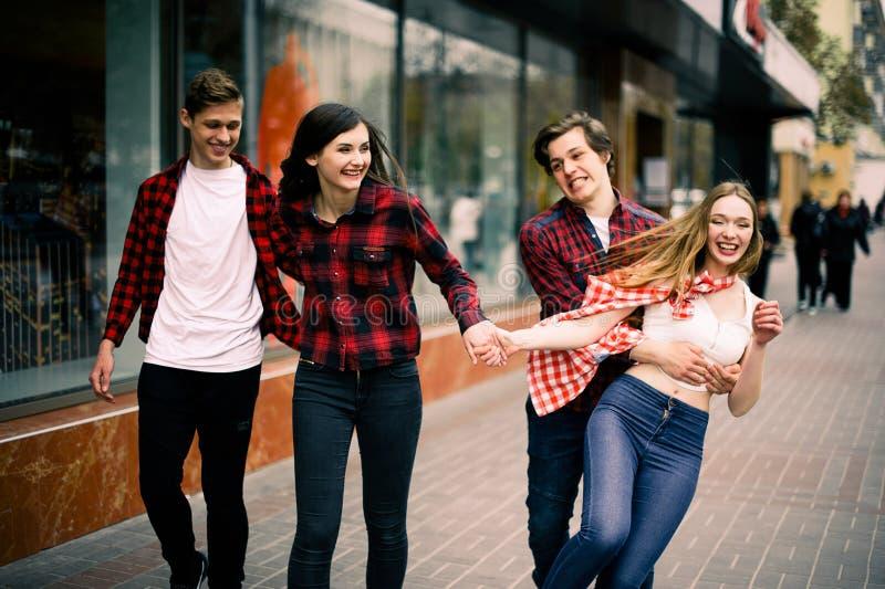 走在城市的四个愉快的时髦少年朋友,谈和微笑 生活方式、友谊和都市生活concep 免版税库存照片