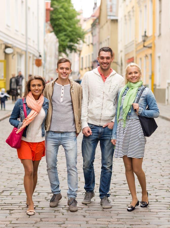 走在城市的小组微笑的朋友 免版税库存图片