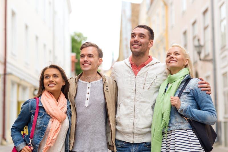 走在城市的小组微笑的朋友 免版税图库摄影
