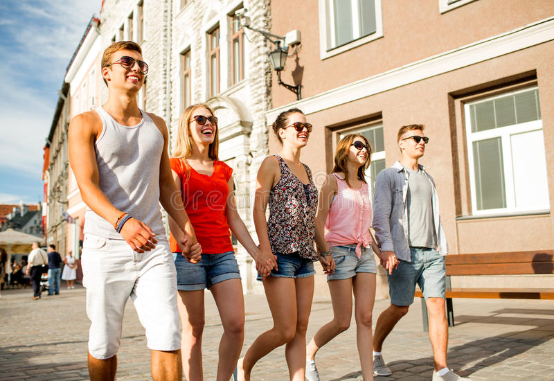 走在城市的小组微笑的朋友 库存图片