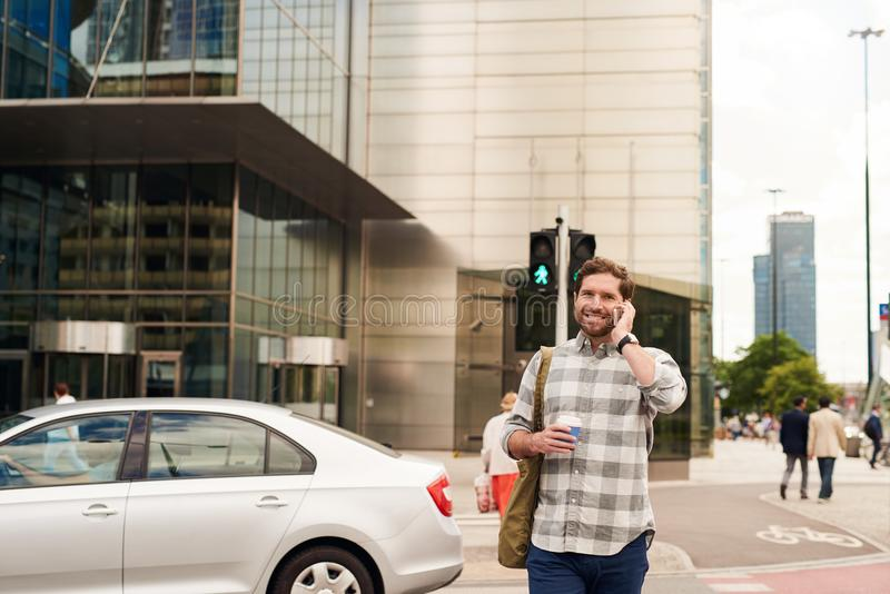 走在城市的微笑的人谈话在手机 免版税库存照片