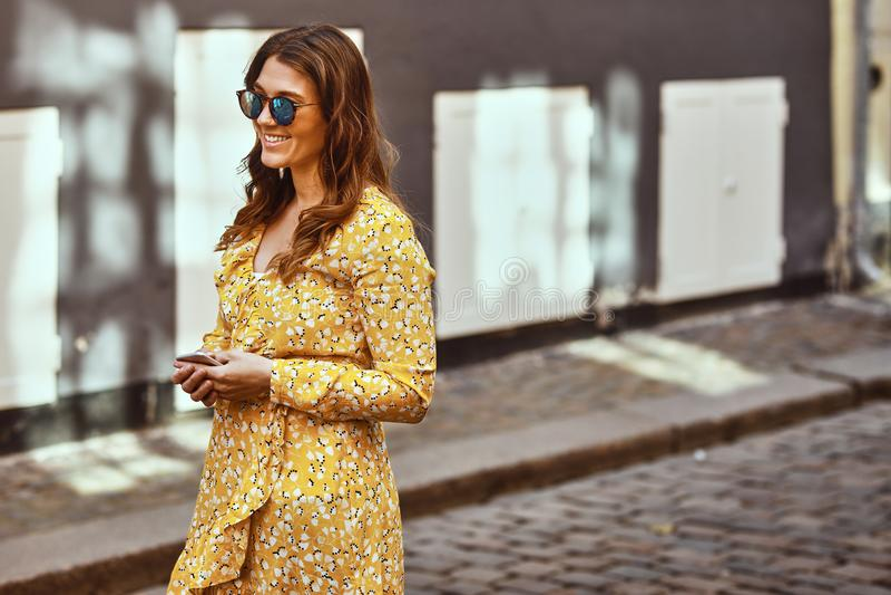 走在城市的微笑的年轻女人拿着手机 库存图片