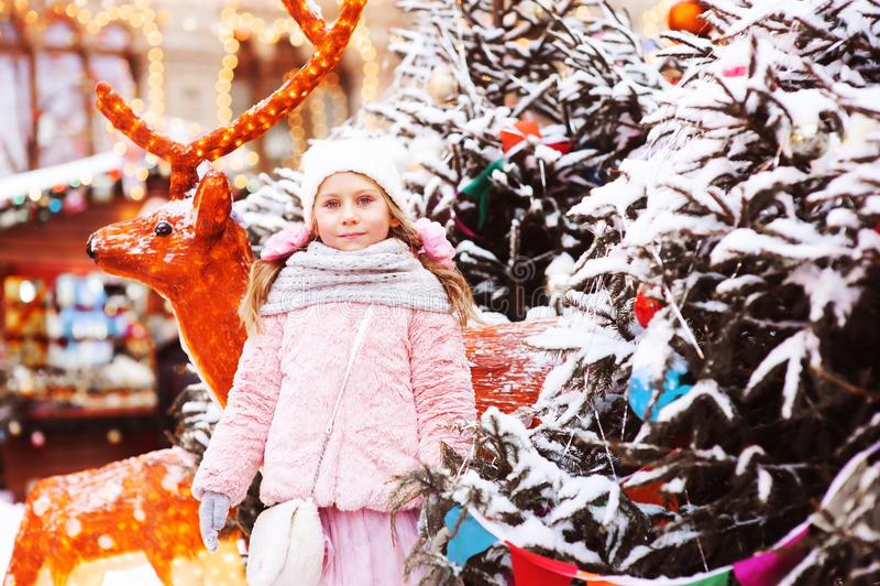 走在城市的愉快的儿童女孩寒假画象装饰圣诞节和新年 免版税库存照片