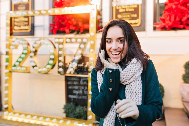 走在城市的时兴的微笑的年轻女人的愉快的冬时,表现出新年心情 典雅的外型,真实 库存图片
